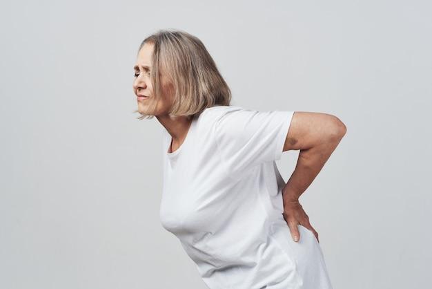 Femme âgée tenant son traitement de la douleur au bas du dos