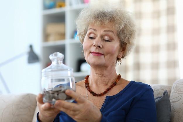 Une femme âgée tient une tirelire avec des pièces