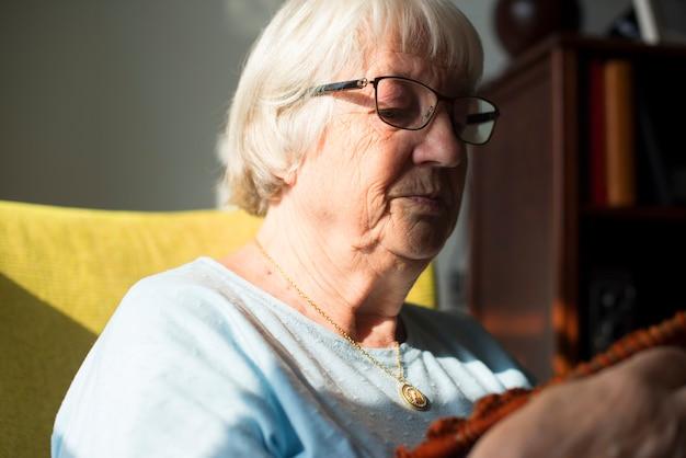 Femme âgée à tricoter pour passe-temps à la maison