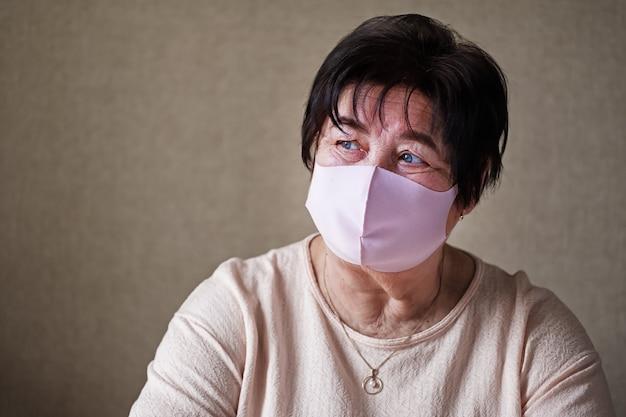 Femme âgée triste avec un masque sur son visage au milieu de la quarantaine et du verrouillage du coronavirus