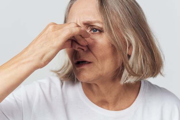 Femme âgée en tshirt blanc douleur problèmes de santé traitement de l'insatisfaction