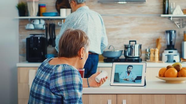 Femme âgée utilisant une application médicale pour parler avec un médecin de sa prescription de pilules. consultation de santé en ligne pour personnes âgées médicaments conseils sur les symptômes, webcam de télémédecine du médecin. médical c