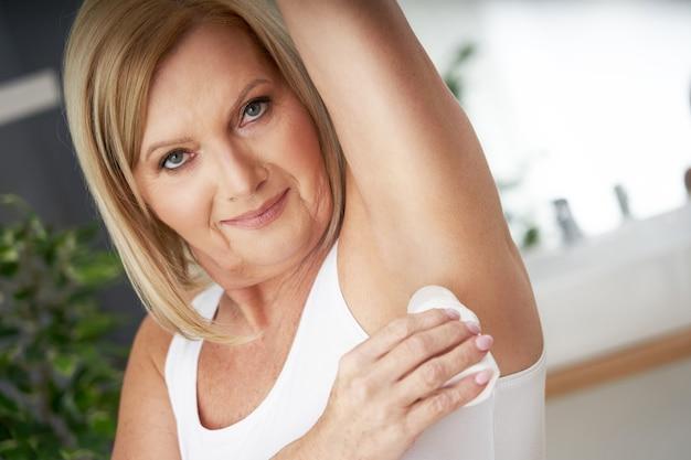 Femme âgée utilisant deo roll-on dans la salle de bain