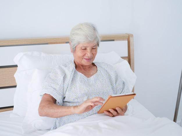 Femme âgée utilisant un ordinateur portable dans la chambre d'hôpital.