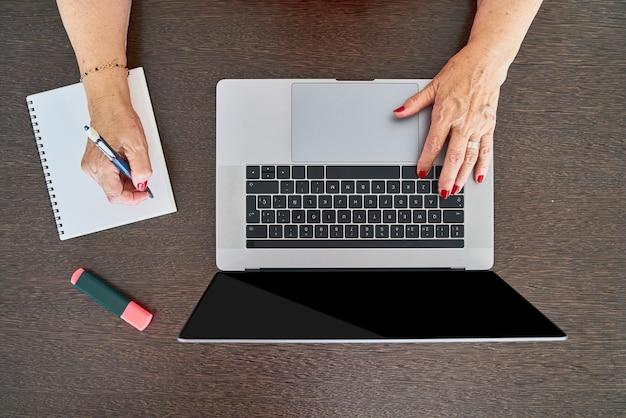 Femme âgée utilisant un ordinateur à son bureau à domicile tout en prenant des notes vue de dessus
