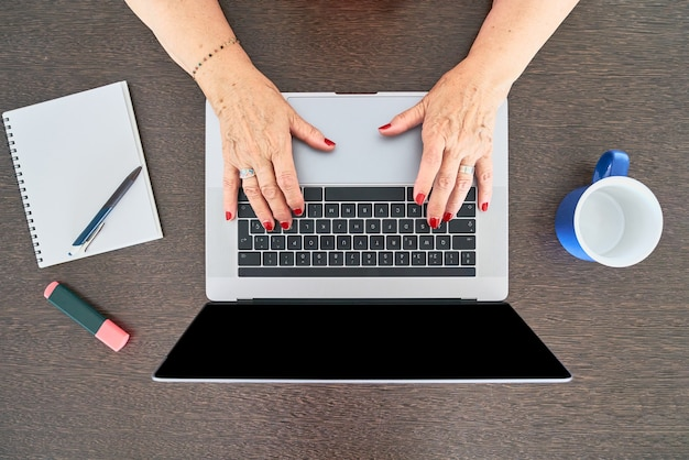 Une femme âgée utilise un clavier d'ordinateur avec les deux mains vue de dessus de la configuration du bureau à la maison