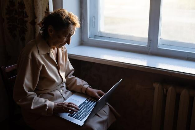 Une femme âgée utilise un ordinateur portable. elle a l'air très surprise. surfer dans un navigateur et les médias sociaux. ordinateur portable sur la table. utilisation de la technologie dans le concept de la vieillesse