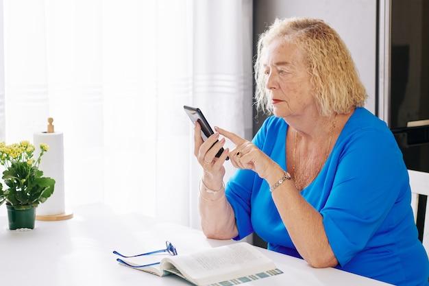 Femme âgée, vérification des messages texte