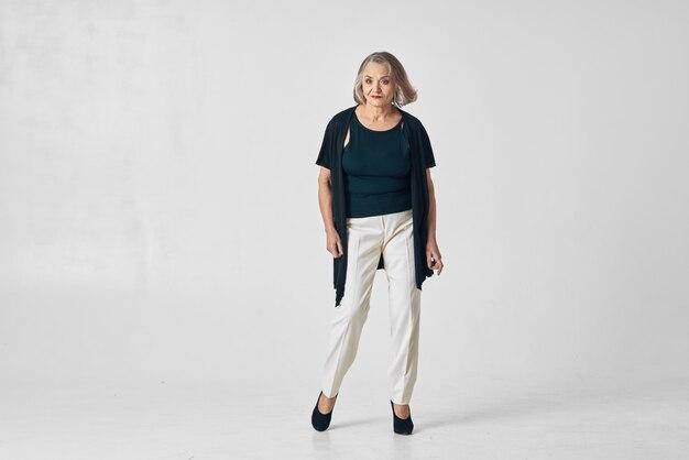 Femme âgée de vêtements à la mode posant studio fond isolé