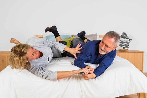 Femme âgée voulant prendre la télécommande d'un homme les mains sur le lit
