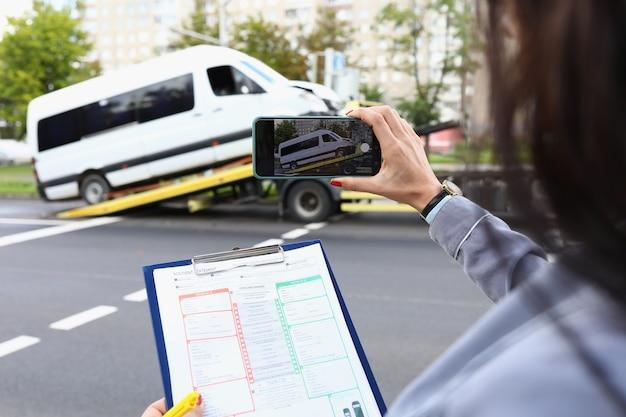 Une femme agent d'assurance filme un minibus cassé sur un smartphone