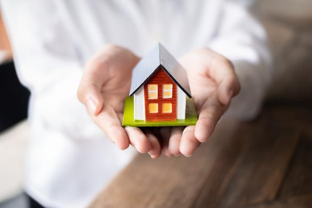 Femme agent immobilier main tenant le modèle de maison, concept immobilier.
