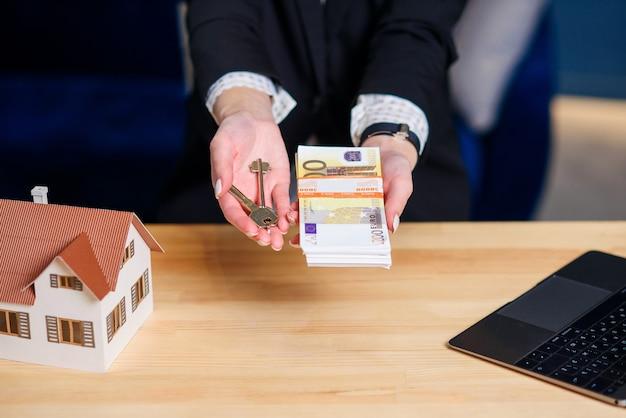 Femme Agent Immobilier Mains Avec Clé De Maison Et Argent. Photo Premium