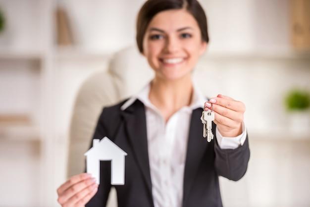 Femme agent immobilier montre maison pour signe de vente et clés.