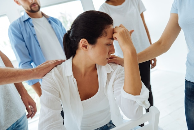 Femme agréable malheureuse réfléchie tenant son front et pensant à sa vie tout en souffrant de dépression