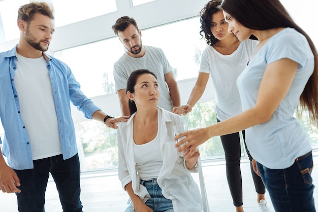 Femme agréable malheureuse sans joie en regardant son ami et en prenant un verre d'eau tout en leur étant reconnaissant pour leur soutien