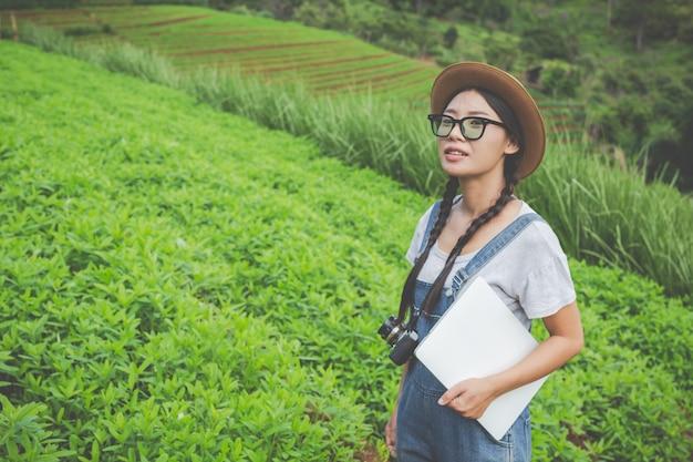 Femme agricole qui inspecte la plante avec des comprimés d'élevage - un concept moderne