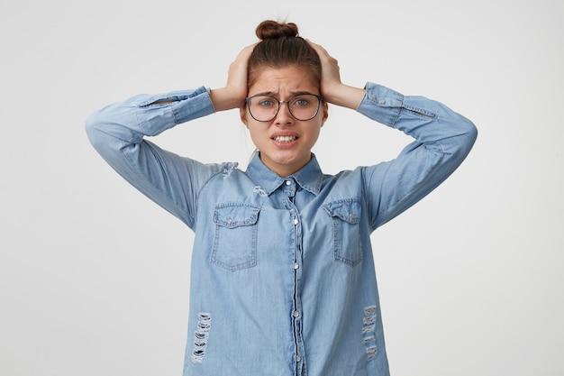 La femme agrippée à sa tête dans une panique de désespoir, ne sait pas où courir ni quoi faire. oh mon dieu, désastre, serra les dents isolées sur un mur blanc.