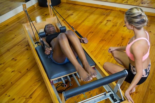 Femme aidant formateur avec pilates sur reformer