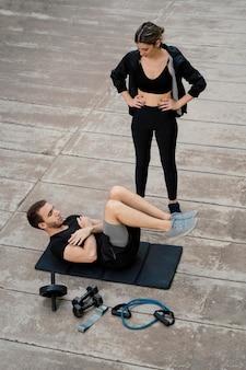 Femme aidant l'homme à faire de l'exercice à l'extérieur