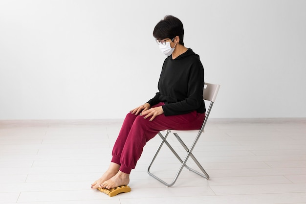 Femme à l'aide d'un appareil de massage des pieds