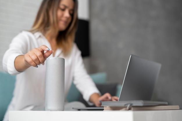 Femme à l'aide d'un assistant numérique de haut-parleur