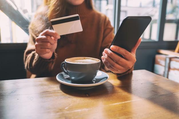 Une femme à l'aide d'une carte de crédit pour acheter et faire des achats en ligne sur téléphone mobile