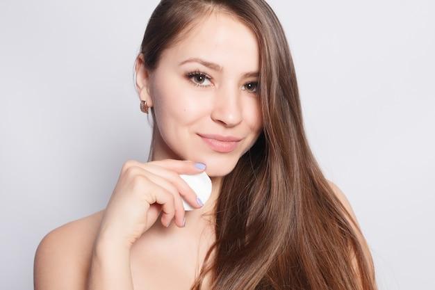 Femme à l'aide d'un coton. heureuse belle jeune femme souriante nettoyant la peau avec un coton. fond clair. belle spa femme souriante. peau fraîche parfaite. concept de jeunesse et de soins de la peau
