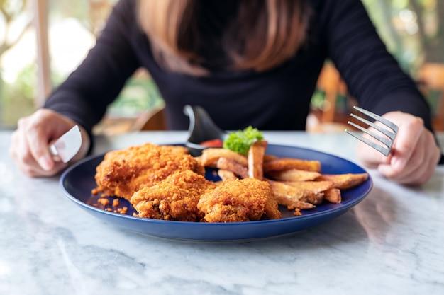 Une femme à l'aide d'un couteau et d'une fourchette pour manger du poulet frit et des frites dans un restaurant