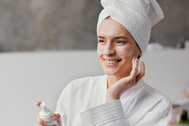 Femme à l'aide d'une crème pour le visage blanche