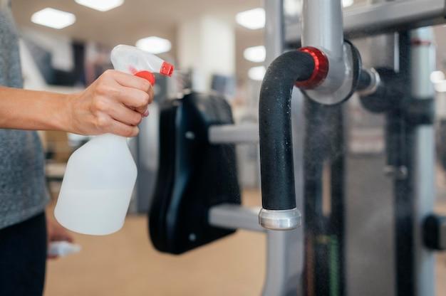 Femme à l'aide de désinfectant sur l'équipement de gym