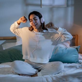 Femme à l'aide d'écouteurs pour la musique à la maison au lit
