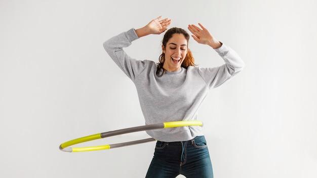 Femme à l'aide de hula hoop à la maison et s'amuser
