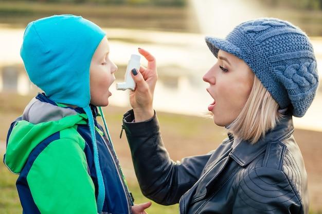 Femme à l'aide d'un inhalateur pour l'asthme à son fils dans un parc d'automne hiver froid
