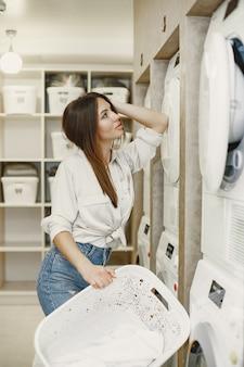 Femme à l'aide de machine à laver faisant la lessive. jeune femme prête à laver les vêtements. intérieur, concept de processus de lavage