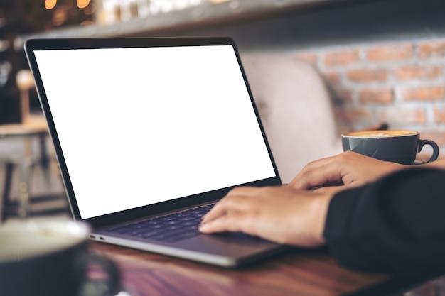 Femme à l'aide de maquette ordinateur portable avec une tasse de café
