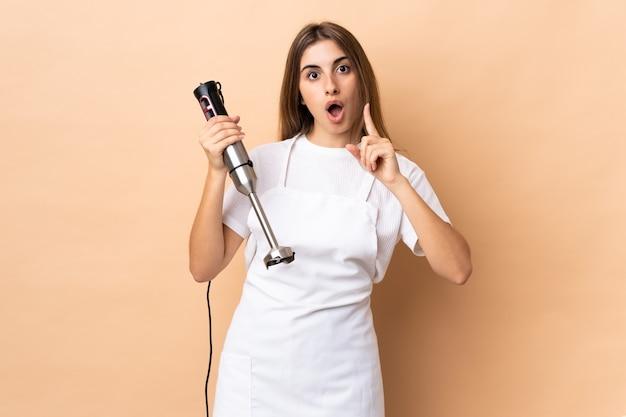Femme à l'aide d'un mixeur à main pensant une idée pointant le doigt vers le haut