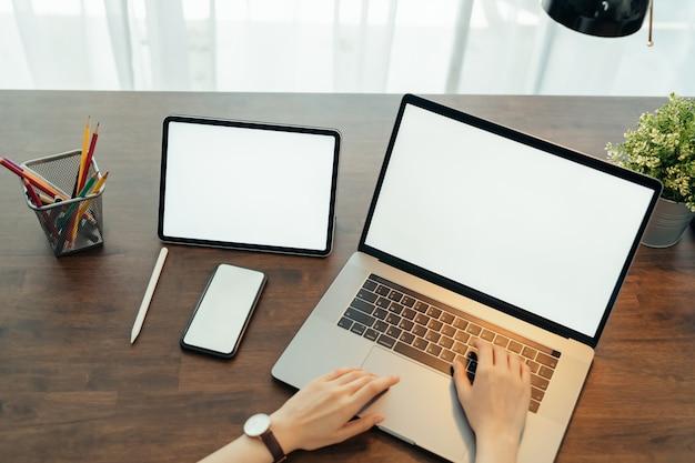Femme à l'aide d'un ordinateur portable numérique et tablette avec smartphone sur la table dans la maison. écran vide pour la publicité