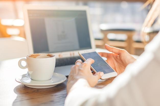 Femme à l'aide d'un ordinateur portable et smartphone au café