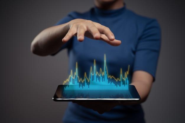 Femme à l'aide de la planification du marketing numérique de tablette avec effet d'hologramme graphique