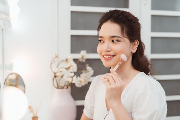Femme à l'aide de rouleau facial de jade pour le massage du visage à la maison.