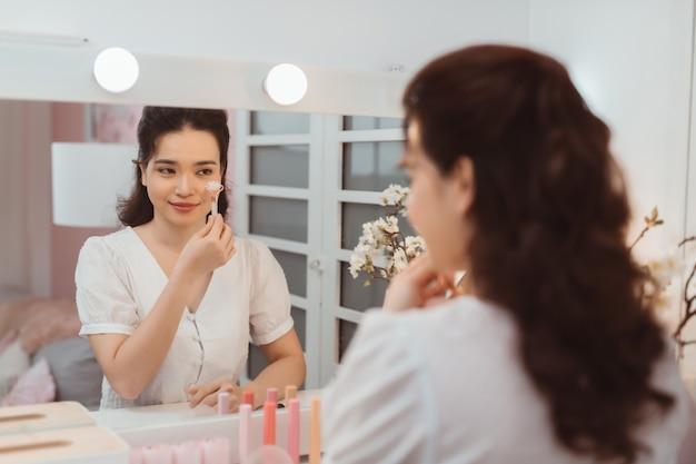 Femme à l'aide de rouleau facial de jade pour les soins de la peau, traitement de beauté quotidien du matin près du bureau