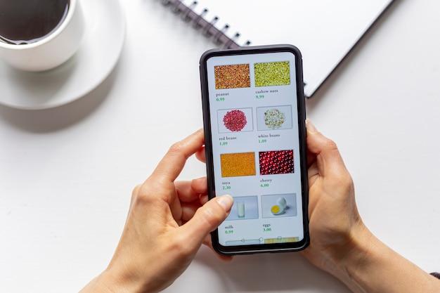 Femme à l'aide de smartphone achète de la nourriture en ligne dans la boutique internet.