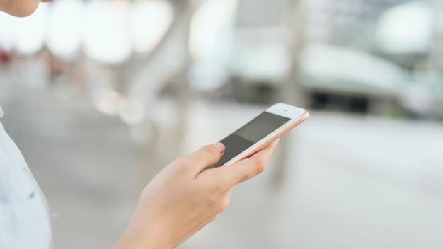 Femme à l'aide de smartphone sur l'escalier dans les espaces publics, pendant les loisirs.