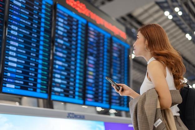 Femme à l'aide de smartphone avec panneau d'information de vol à l'aéroport