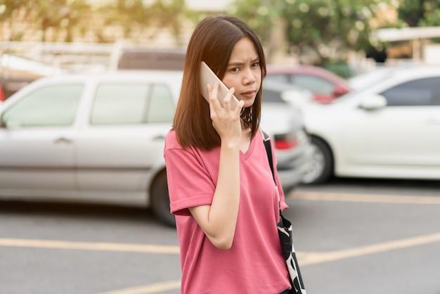 Femme à l'aide de smartphone pour l'application sur la voiture arrière-plan flou.