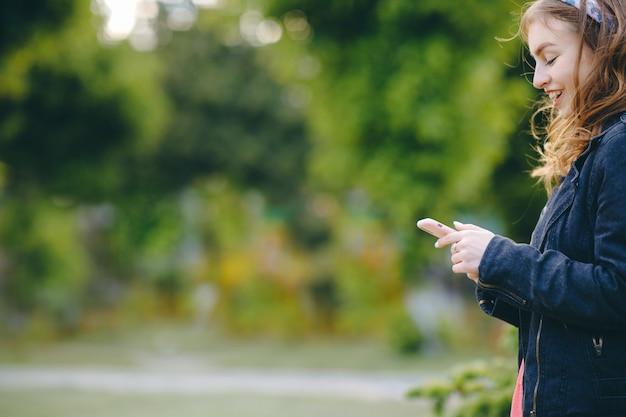 Femme à l'aide de smartphone se détend sur le banc dans le magnifique parc verdoyant