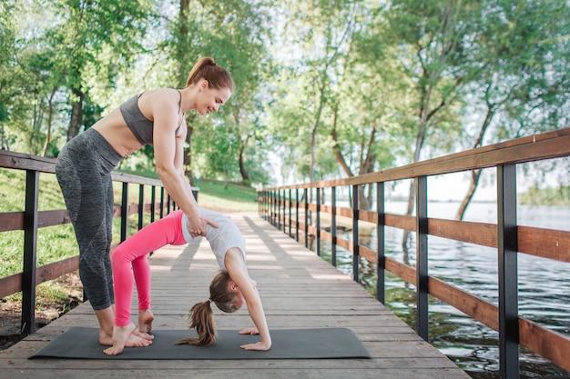 Une femme aide son élève à faire une pose de pont