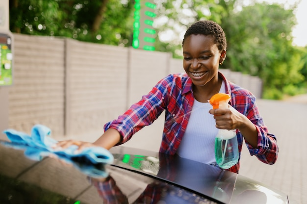 Femme à l'aide de spray nettoyant pour vitres, lave-auto à la main