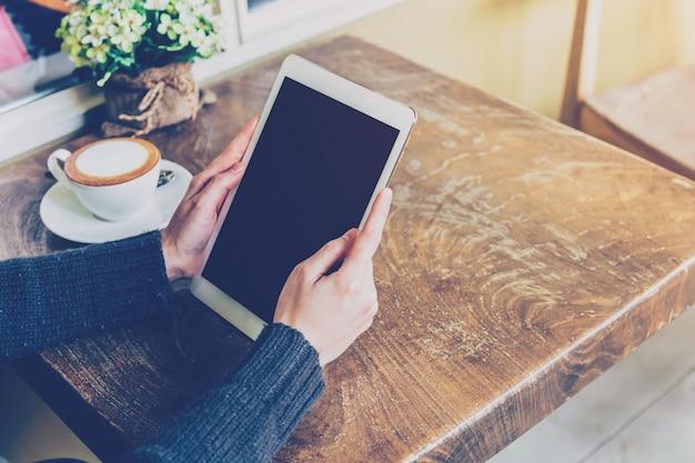 Femme à l'aide de tablette dans un café avec ton vintage.